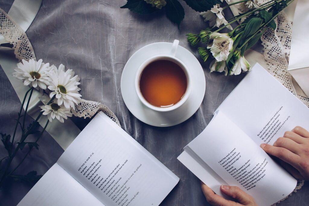 Person der læser bøger og drikker kaffe